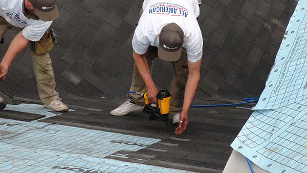 roofers installing shingles on a roof